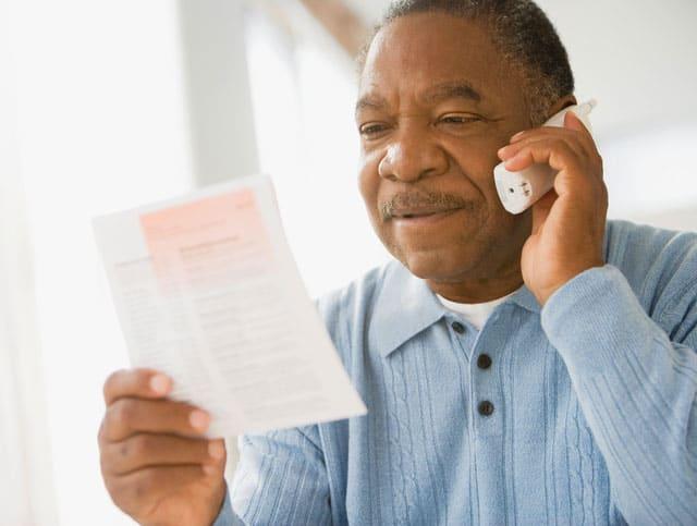 Elderly Man Holding Bill and Talking on Phone