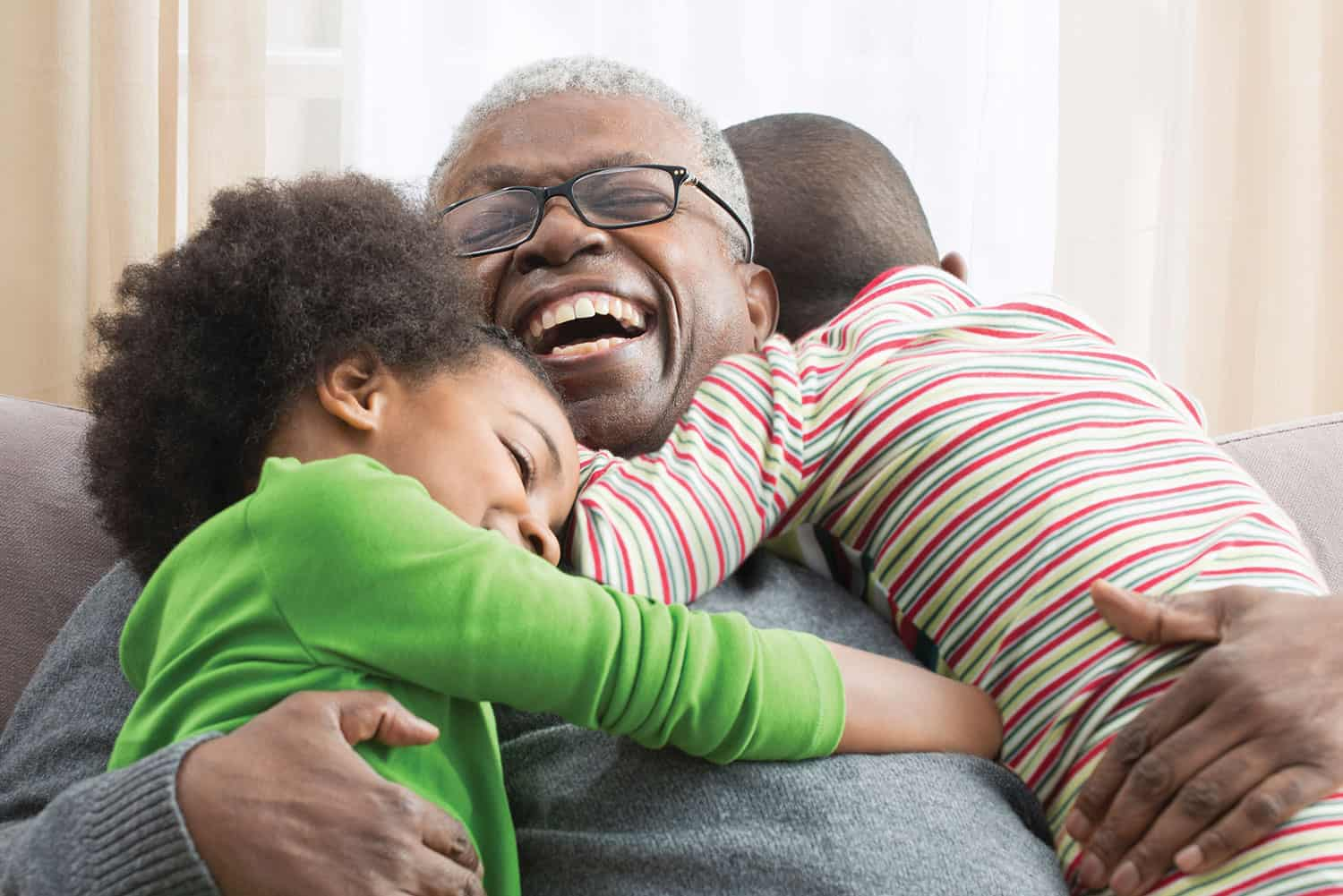 Grandfather Embracing Young Grandchildren on Couch and Laughing