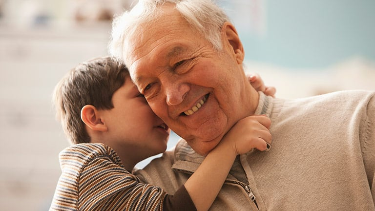 Young Boy Whispering to Grandfather