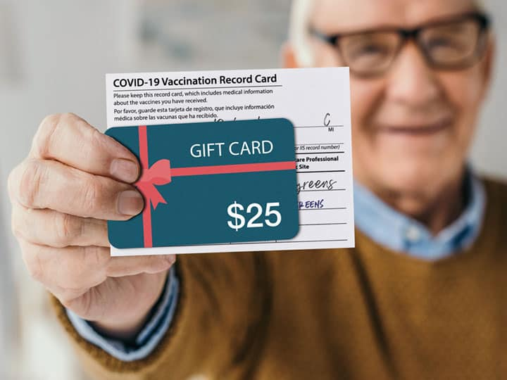 Man holding vaccination card and gift card together